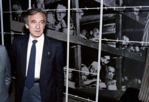"(FILES) This December 18, 1986, file photo shows Nobel Peace prize winner and writer Elie Wiesel (L) standing in front of a photo of himself (bottom 3rd from R) and other inmates, taken at the Buchenwald concentration camp in 1945, during his visit to the Holocaust Memorial Center ""Yad Vashem"" in Jerusalem. Wiesel, the Holocaust survivor, renowned writer and Nobel peace laureate who worked to keep alive the memory of Jews slaughtered during World War II, has died, Israel's Yad Vashem Holocaust centre said on July 2, 2016. / AFP PHOTO / SVEN NACKSTRAND"
